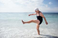 Happy senior woman splashing water with her feet on the beach Stock Photos