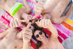 Happy friends lying with thumbs up on the beach Stock Photos