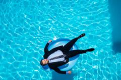 Businessman relaxing on inflatable in swimming pool Stock Photos