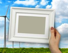 Wooden frame in woman hands. wind mill turbine in a farmland on the backgroun Stock Photos