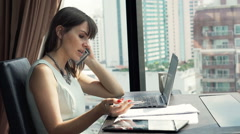 Angry businesswoman with laptop and documents talking on cellphone in office Stock Footage