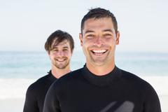 Handsome men wearing wetsuits on the beach Stock Photos