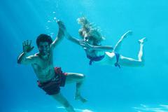Happy couple swimming underwater in swimming pool Stock Photos