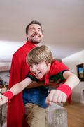 Father and son pretending to be superhero in living room at home Stock Photos