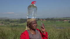 African Zulu woman speaking on mobile phone balancing water on head Stock Footage