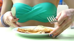 the Girl in the Green Bathing Suit Eating With a Fork and Knife. She Sits in a - stock footage
