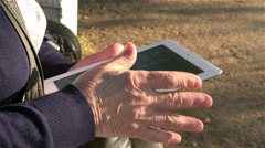 Hands of an old woman slip on the touch screen of the new tablet white Stock Footage
