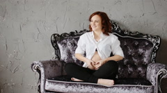 Attractive pregnant woman with the red hair. Sitting on a vintage sofa. Stock Footage