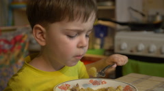 Boy of three years in the yellow shirt is eating Stock Footage