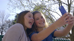 Best Friends Take A Cute And Funny Selfies Together On Park Bench, Then Text It Stock Footage