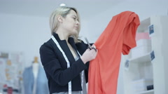 4K Dressmaker at work in her studio, creating new designs - stock footage