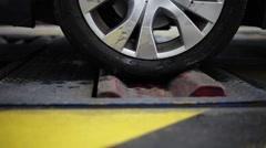 Car entering brake tester in a workshop, slider shot Stock Footage