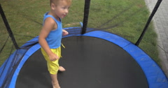 Child jumping inside protected outdoor tramp Stock Footage