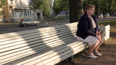 Beautiful cute elderly woman sitting on a park bench blue Stock Footage