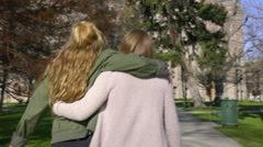 Teens Walk With Arms Around Each Other, They Push Each Other And Laugh Stock Footage