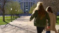 Two Playful Teens Walk Away From Camera Down Steps, Through City Park Stock Footage