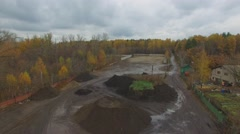 Loaders and truck works among plants on Elk Island at autumn Stock Footage