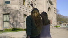 Two Teen Girls Walk Past Old City Building And Point Out Details To Each Other Stock Footage
