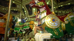 Lighting of amusement carousel with fancy painted horses at night, 4K Stock Footage