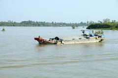 Working barges on the Mekong Rive - stock photo