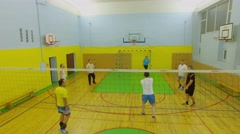 Group of adult people play volleyball in gym. Stock Footage