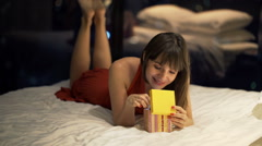 Elegant woman opening gift box lying on bed at home at night Stock Footage