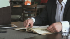 Businessman looks at food menu of the restaurant Arkistovideo
