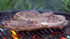 Turning steak on barbecue grill - slow motion - stock footage