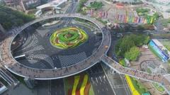 Transport traffic on roundabout under round pedestrian bridge Stock Footage