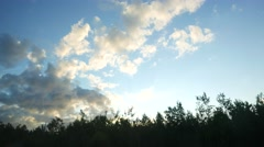 Bright and gray clouds on blue sky, view from moving vehicle, dark tree tops Stock Footage
