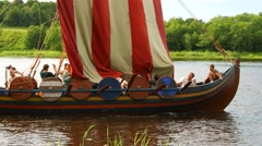 Crew strike down striped sail at traditional viking longship boat, small vessel Stock Footage
