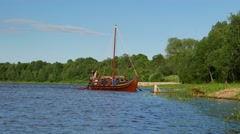Viking longship boat coasting to river bank, sail using long oars, green shore Stock Footage