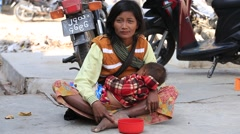 Poor woman with child begging money from people on the street, Myanmar. Burma Stock Footage
