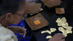 Gold leaf production by creating equal piece of an extremely thin unbroken sheet Stock Footage