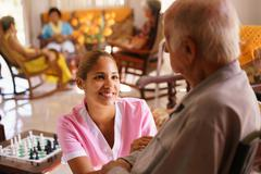 Hospice Nurse Helping Elderly Man On Wheelchair - stock photo