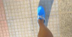 Male feet in blue shoes walking on street Stock Footage