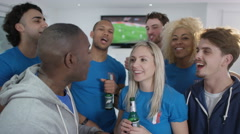4K Excited group of friends watching sports game on bar TV screen - stock footage