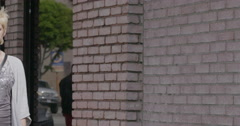 Front view of young woman walking past walls in Downtown LA 4K Stock Footage
