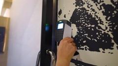 Woman swipes a key card on a secure door Stock Footage