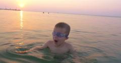 Little child in goggles having fun in sea during sundown Stock Footage