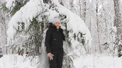 Girl has fun with snow in the winter forest Stock Footage