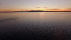 Aerial Drone Footage Flying away from sunset across puget sound waters Stock Footage