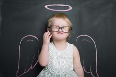 Girl over chalkboard with funny angel wings and nimbus Stock Photos