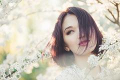 Girl with Cherry Blossom. Young Woman next Sakura - stock photo