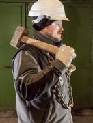 Tough worker with iron chain and sledgehammer - stock photo