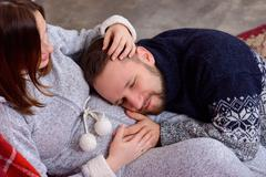 Happy husband listens to baby heartbeat lying on belly of his pregnant wife Stock Photos