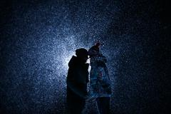 Silhouette Man and girl at night under the snow. Stock Photos