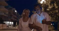 Senior couple listening to music during night walk Stock Footage