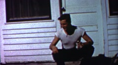 1958: Wild teenager smoking cigarette drinking beer calling dog. Stock Footage