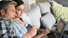 Couple in sofa websurfing and shopping on internet - stock footage